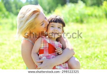 Portrait of happy smiling mother and child having fun together outdoors in summer sunny day - stock photo