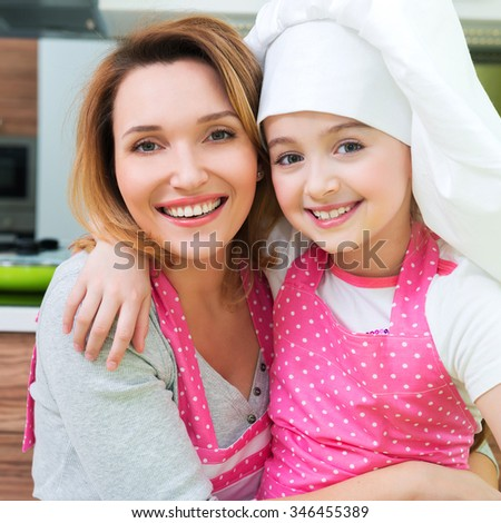 Portrait of happy smiling mother and daughter in pink apron at the kitchen. - stock photo