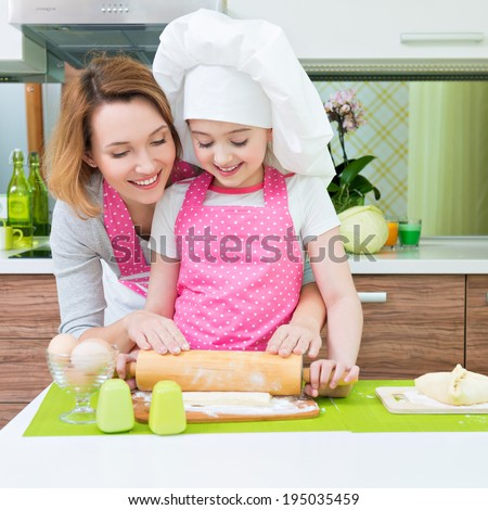 Portrait of happy smiling mother and daughter making pies together at the kitchen. - stock photo