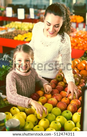 Portrait of happy smiling mother and little daughter buying ripe apples at the market. Focus on girl