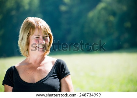 Portrait of happy smiling senior woman - outside on sunny day - stock photo