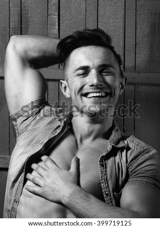 Portrait of happy smiling sexy sensual muscular young macho man with bare torso and stylish hair in jeans shirt indoor on wooden background, vertical picture - stock photo