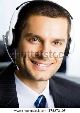 Portrait of happy smiling support phone operator in headset at workplace - stock photo