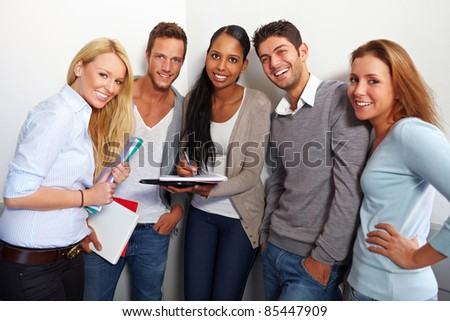 Portrait of happy smiling university students in the hall - stock photo