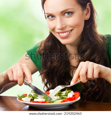 Portrait of happy smiling woman eating salad on plate, outdoor - stock photo