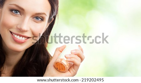 Portrait of happy smiling woman showing bottle with pills, outdoor, with blank area for copyspace - stock photo