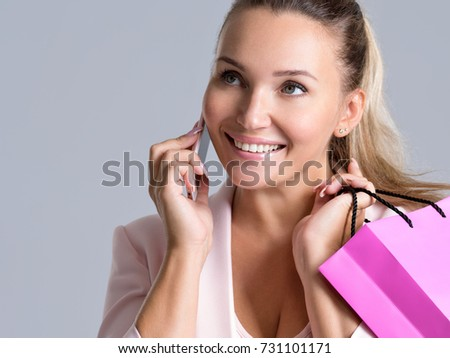 Portrait of happy smiling woman with pink shopping bag that speaks on a mobile phone. Attractive cheerful female holds the  bag with purchasing.