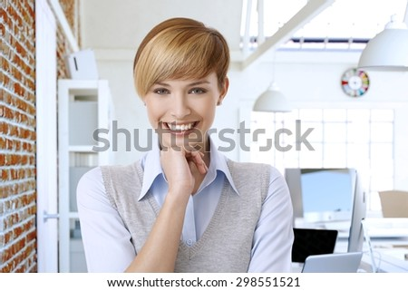 Portrait of happy smiling young attractive woman with short hair, hand on chin, looking at camera. - stock photo