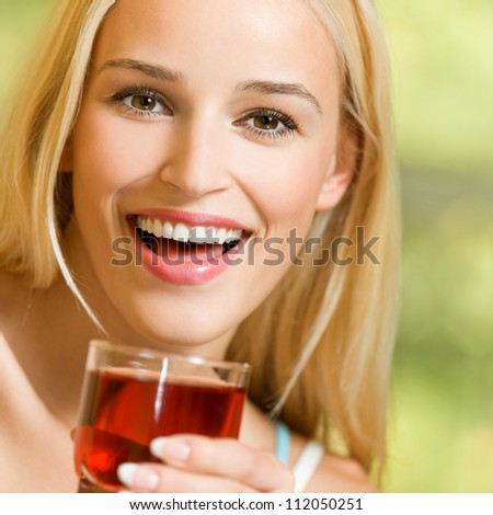 Portrait of happy smiling young beautiful blond woman drinking garnet juice - stock photo
