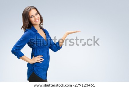 Portrait of happy smiling young beautiful businesswoman showing something or blank copyspase for product or sign text - stock photo