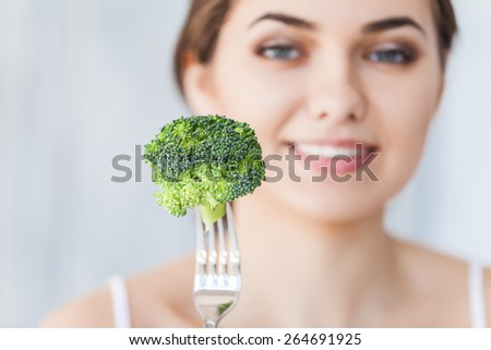 Portrait of happy smiling young beautiful woman eating broccoli - stock photo