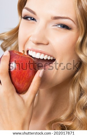 Portrait of happy smiling young beautiful woman eating red apple, over gray background - stock photo