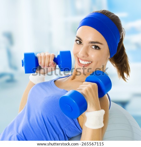 Portrait of happy smiling young beautiful woman exercising, at fitness club or center - stock photo