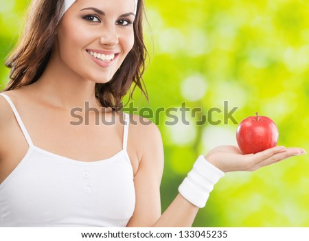 Portrait of happy smiling young beautiful woman in fitness wear with apple, outdoors - stock photo