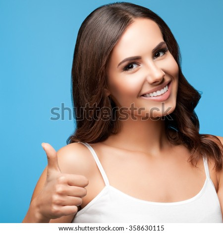 Portrait of happy smiling young beautiful woman in white casual clothing, showing thumbs up gesture, over blue background - stock photo