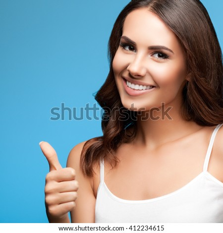 Portrait of happy smiling young beautiful woman in white casual clothing, showing thumbs up gesture, over blue background