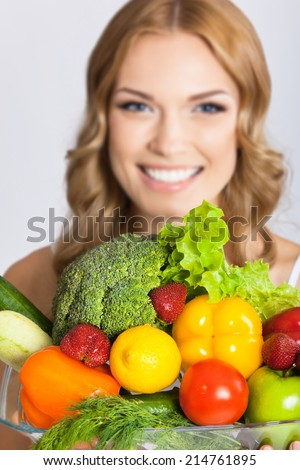 Portrait of happy smiling young beautiful woman with healthy vegetarian raw food, over gray. Selective focus on food.