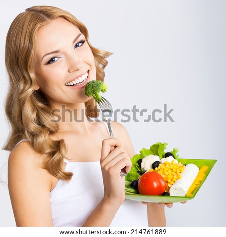 Portrait of happy smiling young beautiful woman with healthy vegetarian salad, over gray background - stock photo