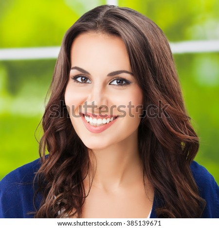 Portrait of happy smiling young brunette woman - stock photo
