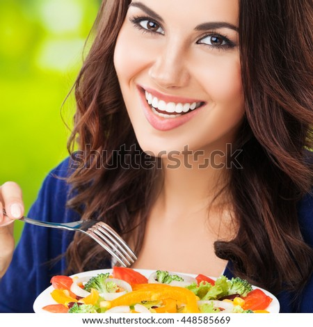Portrait of happy smiling young brunette woman with vegetarian vegetable salad