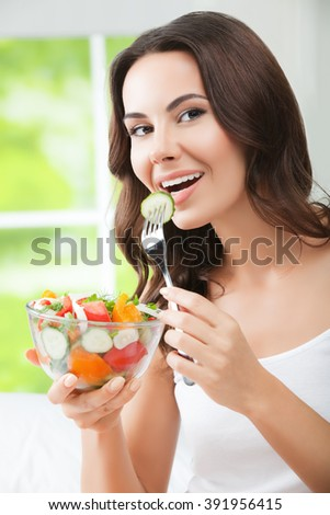 Portrait of happy smiling young brunette woman with vegetarian vegetable salad, indoors. Healthy eating, beauty and dieting concept. - stock photo