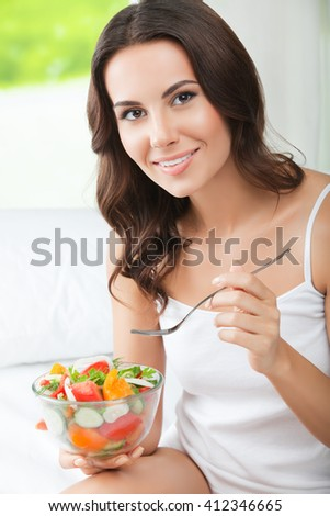 Portrait of happy smiling young brunette woman with vegetarian vegetable salad, indoors. Healthy eating, beauty and dieting concept.