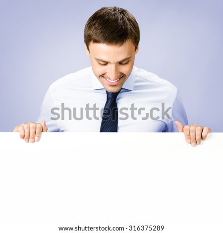 Portrait of happy smiling young business man showing blank signboard, over violet background - stock photo