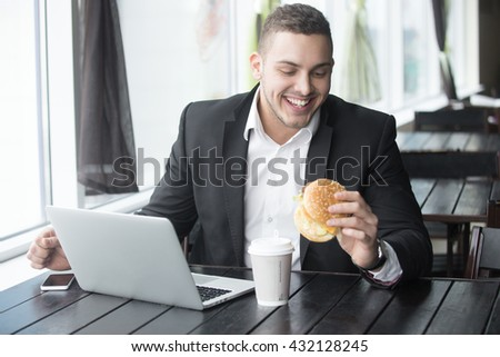 Portrait of happy smiling young business man sitting with glass of drink and hamburger in fast food restaurant interior. Attractive caucasian man eating and using notebook computer in cafe. Indoors - stock photo