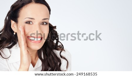 Portrait of happy smiling young business woman covering with hand her mouth, against grey background, with copyspace