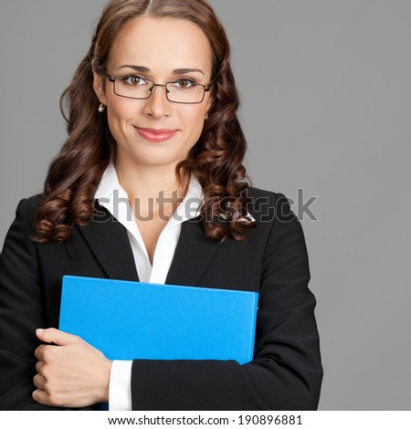 Portrait of happy smiling young business woman with blue folder, over gray background - stock photo