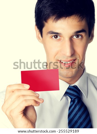 Portrait of happy smiling young businessman giving blank red business or plastic credit card with copyspace area for text or slogan