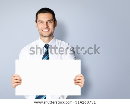 Portrait of happy smiling young businessman showing blank signboard with copyspace area for slogan or text message, posing at studio, against grey background