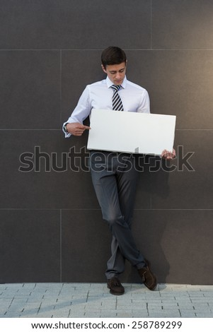 Portrait of happy smiling young businessman showing blank signboard, with copyspace area for text or slogan, against grey wall background outdoors - stock photo