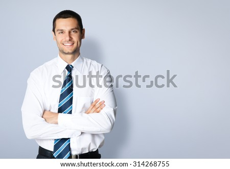 Portrait of happy smiling young businessman with crossed arms pose, posing at studio, against grey background, with blank copyspace area for slogan or text message - stock photo