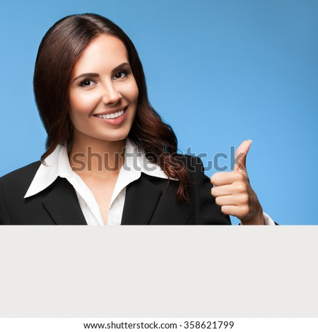 Portrait of happy smiling young businesswoman in black suit, showing blank signboard, over blue background, showing thumb up gesture - stock photo