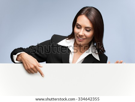 Portrait of happy smiling young businesswoman in black suit, showing blank signboard with blank copyspace area for slogan or text, over grey background - stock photo