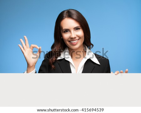 Portrait of happy smiling young businesswoman in black suit, showing blank signboard with blank copyspace area for slogan or text, over blue background, showing okay gesture
