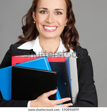 Portrait of happy smiling young busy business woman with folders, over gray background