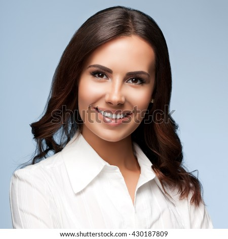 Portrait of happy smiling young cheerful brunette businesswoman, over grey background - stock photo