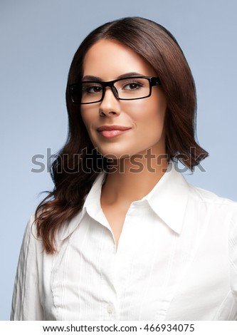 Portrait of happy smiling young cheerful brunette businesswoman, over grey background