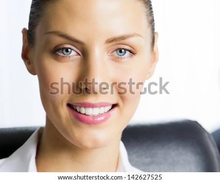 Portrait of happy smiling young cheerful business woman at office - stock photo