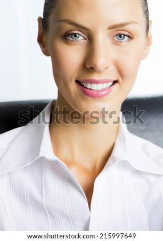 Portrait of happy smiling young cheerful businesswoman at office