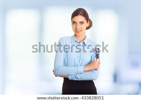 Portrait of happy smiling young cheerful businesswoman in blue clothing. With glasses in crossed arms pose. - stock photo