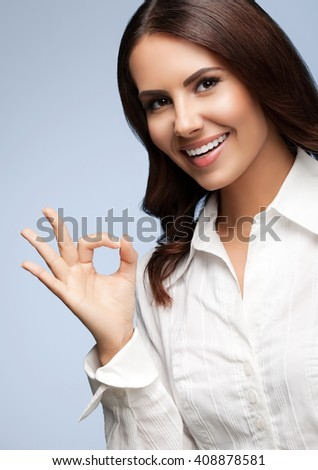 Portrait of happy smiling young cheerful businesswoman, showing okay hand sign gesture, on grey - stock photo