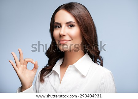 Portrait of happy smiling young cheerful businesswoman, showing okay hand sign gesture, over grey background