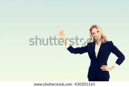 Portrait of happy smiling young cheerful businesswoman, showing something or blank copyspace area for slogan or text message, with blank copyspace area for text or slogan - stock photo
