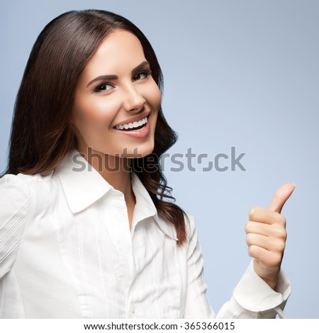 Portrait of happy smiling young cheerful businesswoman, showing thumb up hand sign gesture, on grey background - stock photo