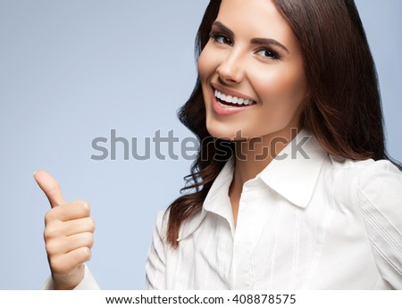 Portrait of happy smiling young cheerful businesswoman, showing thumb up hand sign gesture, on grey background