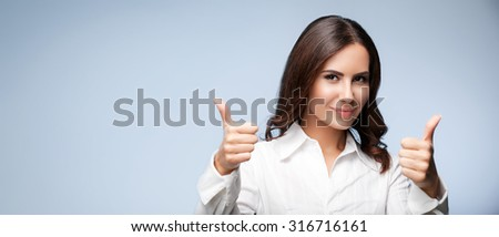 Portrait of happy smiling young cheerful businesswoman, showing thumb up hand sign gesture, with blank copyspace area for slogan or text message, over grey background - stock photo