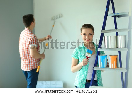 Portrait of happy smiling young couple  painting interior wall of new house - stock photo